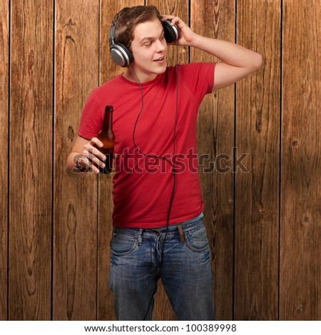 portrait of a young man listening to music and holding a beer against a wooden wall