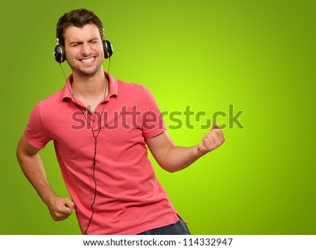 Portrait Of A Young Man Listening To Music On A Green Background