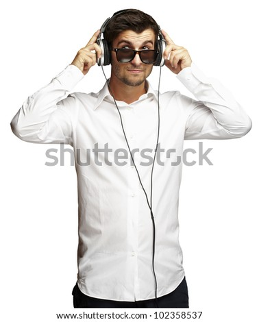 portrait of a young man listening to music using headphones over a white background