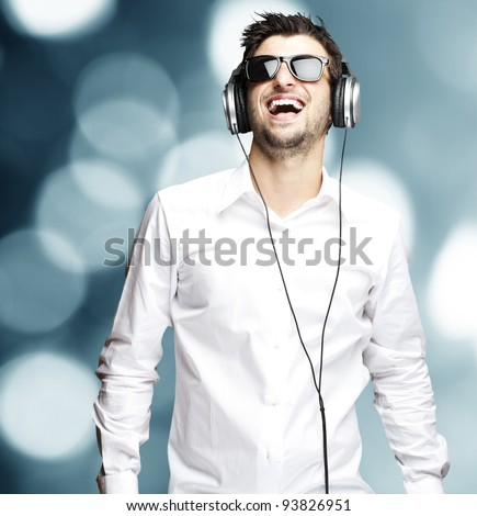 portrait of a young man listening to music with headphones against an abstract background stock photo