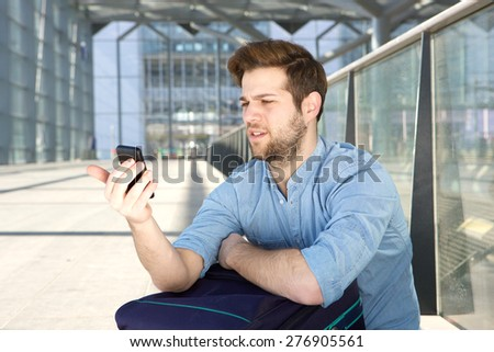 Portrait of a young man looking at mobile phone with confused expression on face