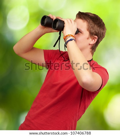 portrait of a young man looking through binoculars against a nature background