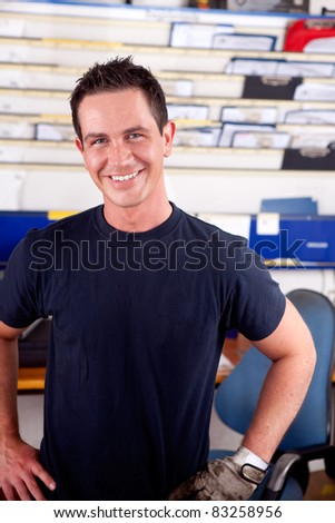 Portrait of a young man mechanic smiling, looking at the camera