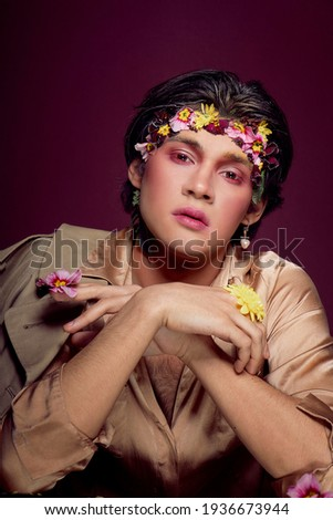 portrait of a young man of Asian appearance with flowers on his head.flowers boy Stok fotoğraf ©