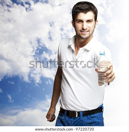 portrait of a young man offering water against a cloudy sky background
