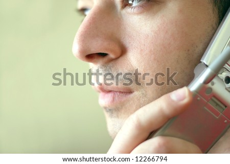 Portrait of a young man on his cell phone.  He is listening with a  serious look of concern on his face.