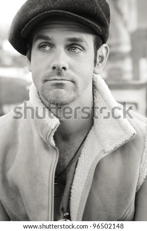 Portrait of a young man outdoors in sepia tones wearing hat and vest