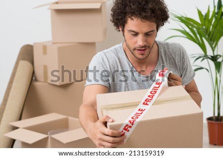 Portrait Of A Young Man Packing Cardboard Box With Fragile Sellotape