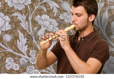 Portrait Of A Young Man Playing Flute On Wallpaper