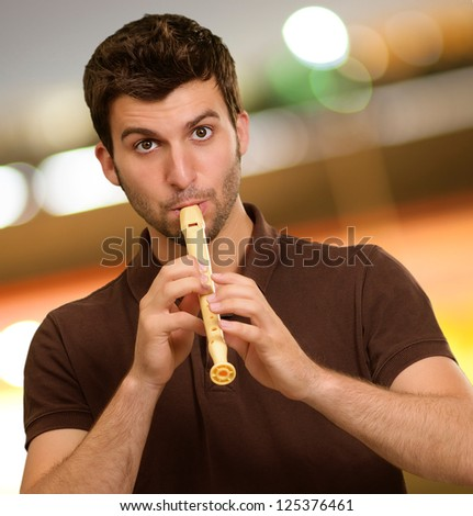 Portrait Of A Young Man Playing Flute, Outdoors