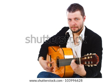 Portrait of a young man playing the guitar, looking into camera - isolated on white