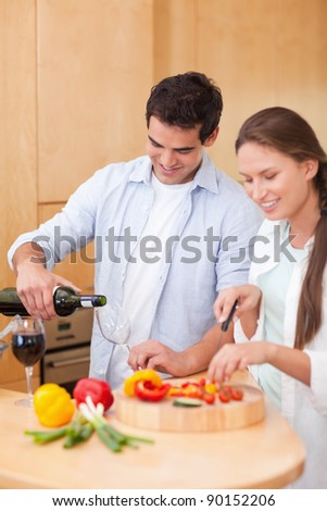 Portrait of a young man pouring a glass of wine while his wife is cooking in their kitchen
