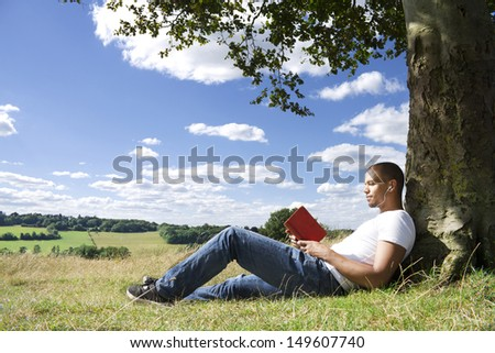 Portrait of a Young Man Reading a Book Outdoors in the Countryside