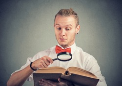 Portrait of a young man reading an interesting book with magnifying glass