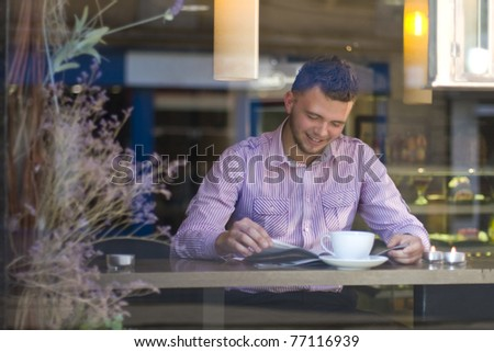 Portrait of a young man reading and drinking coffee