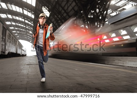 Portrait of a young man running in a train station