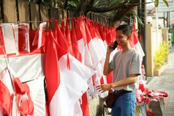 portrait of a young man selling flags taking orders from a telephone
