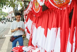 portrait of a young man selling the Indonesian national flag