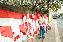 portrait of a young man selling the Indonesian national flag beside street