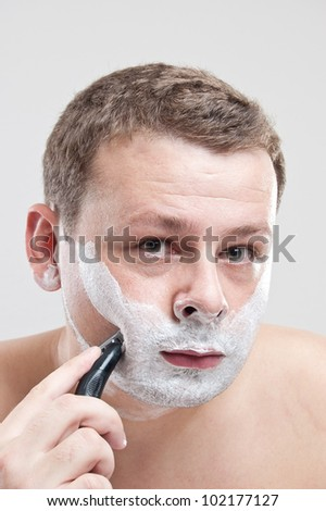 portrait of a young man shaving his face