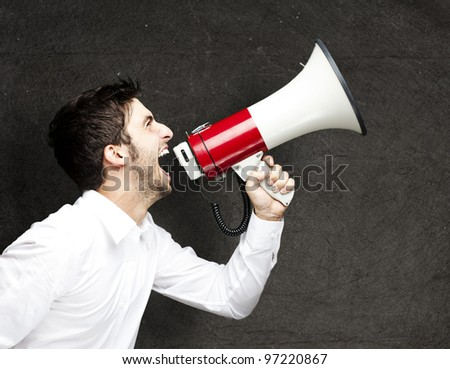portrait of a young man shouting using a megaphone against a grunge wall
