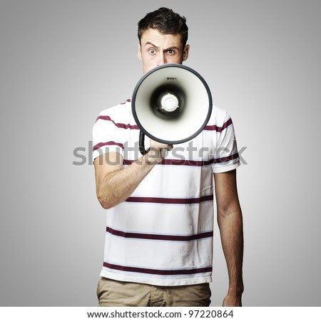 portrait of a young man shouting using a megaphone over a grey background