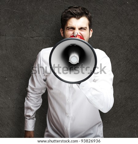 portrait of a young man shouting with a megaphone against a black background