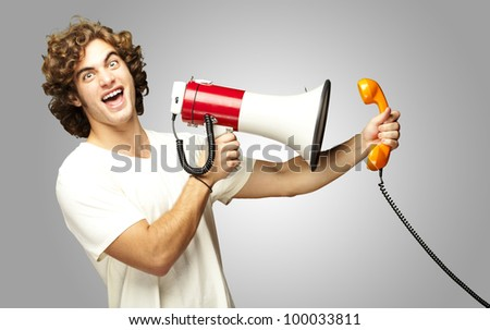 portrait of a young man shouting with a megaphone and talking on a vintage telephone over a grey background
