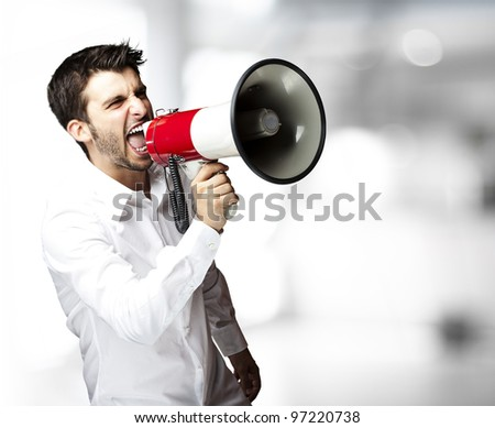 portrait of a young man shouting with a megaphone indoor