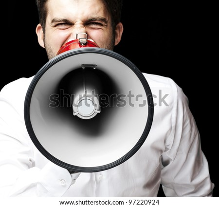 portrait of a young man shouting with a megaphone over a black background