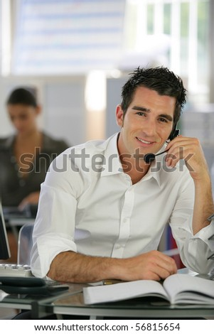 Portrait of a young man sitting at a desk with a headset
