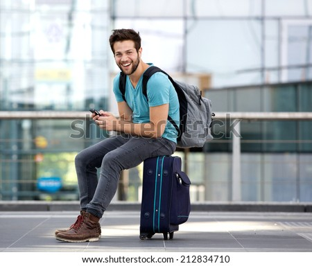 Portrait of a young man sitting on suitcase and sending text message  #212834710