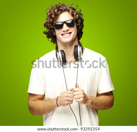 portrait of a young man smiling with headphones over a green background stock photo