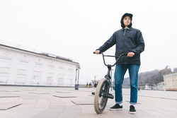 Portrait of a young man standing with a BMX bike against the city background. BMX rider stands with a bike. BMX concept