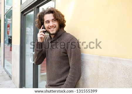 Portrait of a young man using a cell phone to make a call while standing by an office building entrance, outdoors.