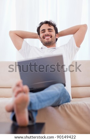 Portrait of a young man using a laptop in his living room