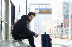 Portrait of a young man waiting for train with suitcase travel bag