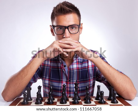 Portrait of a young man waiting for your move. Chess opponent looking provocatively into your eyes.