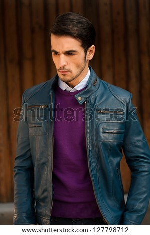 portrait of a young man wearing blue leather jacket against grunge wooden door