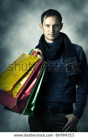 Portrait of a young man wearing scarf and dark blue shirt after shopping with bags