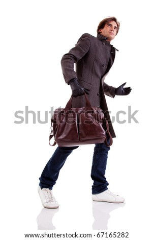 Portrait of a young man with a handbag, hasty, in autumn/winter clothes, isolated on white. Studio shot