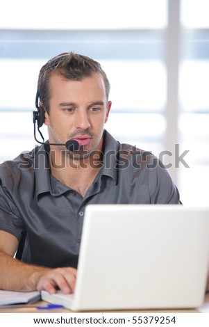 Portrait of a young man with a headset in front of a laptop computer