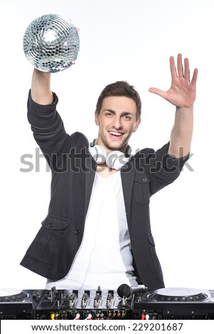 Portrait of a young man with a mirror ball and dj mixer on a white background.
