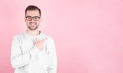 Portrait of a young man with a smile points his index finger towards copyspace