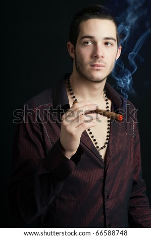 Portrait of a young man with cigar and smoke, studio shot