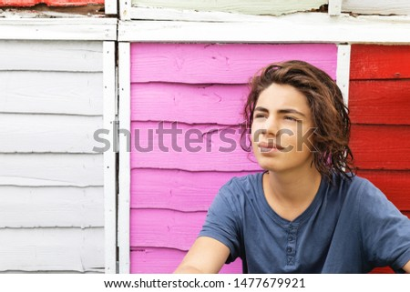 Portrait of a young man with colored fence behind. Frontal view. Nobody inside