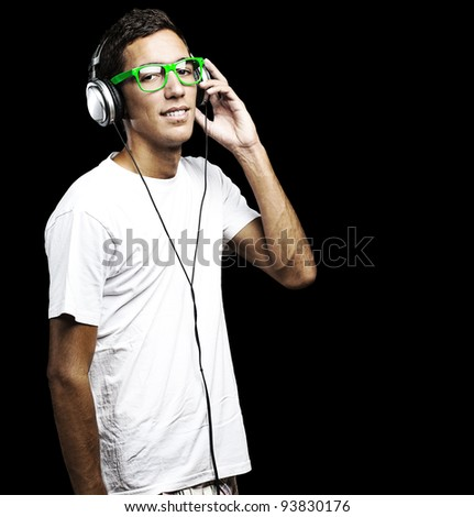 portrait of a young man with green glasses listening to music with headphones against a black background