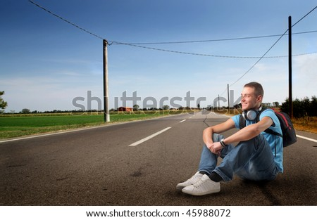 Portrait of a young man with headphones and a rucksack sitting on a countryside road - stock photo