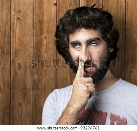 portrait of a young man with his finger in his nose against a wooden wall