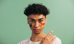 Portrait of a young man with LGBT flag painted on his cheeks. Theme of equality and freedom of choice.